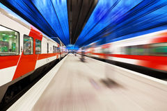 Passenger train passing railway station Royalty Free Stock Images