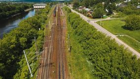 Train on the railway. Passenger train on a railway in a rural country. Aerial view train, railway, highway. Aerial drone footage, 4k stock video