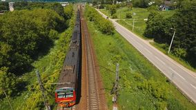 Train on the railway. Passenger train on a railway in a rural country. Aerial view train, railway, highway. Aerial drone footage, 4k stock footage