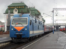 Passenger train at the railway station of Khabarovsk. Blue locomotive and grey coaches Stock Image