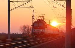 Passenger train on railway at sunset Stock Photos