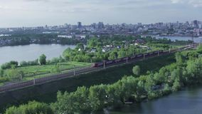 Passenger train rides on city background summer. Passenger train rides on city background stock video footage