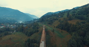 Passenger train rides on the railway bridge across mountain river stock footage