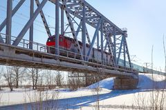 Passenger Train rides on the railway bridge. Passenger Train rides in winter on the railway bridge royalty free stock photo