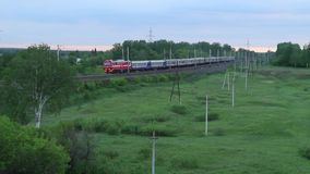 Passenger train running in the countryside among green trees, Russia. Trans-Siberian Railway stock footage