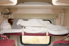 Passenger train sleeping on top shelf of the side seats in the second-class carriage turned to the wall Royalty Free Stock Photo