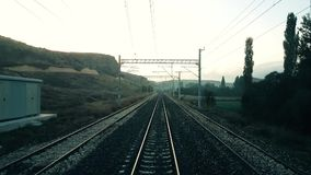 Passenger train slowing down and stops on the railroad. In the morning, view from the rear of train stock video