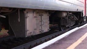 Passenger train wheel passes platform. Close-up of passenger train wheel passes platform on summer day stock footage