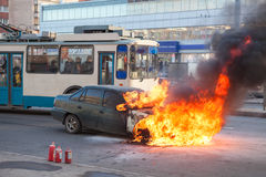 Passenger transport passes near burning car Stock Image