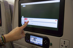 Passenger using entertainment screen in plane Stock Image