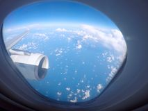 Passenger view through the window of a jet plane showing sky, clouds, jet engine and wing.  royalty free stock photos