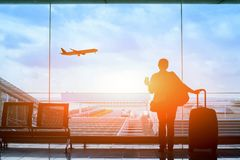 Passenger waiting for flight in airport, departure terminal. Happy traveler waiting for the flight in airport, departure terminal, immigration concept royalty free stock images