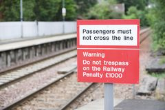 Passenger warning sign at railway train station stating do not trespass or penalty fine will be issued if you cross the rail line. Uk royalty free stock photos