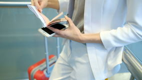 Passenger in a white suit checks the documents and holding a phone. stock footage