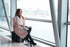 Passenger woman in airport waiting for air travel. Royalty Free Stock Photos