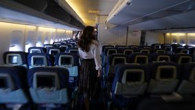 Passenger woman walk in airplane aisle, go out of boing airliner. Barcelona, Spain - AUGUST 11 2018: Passenger young woman walk in airplane aisle. Tourist girl stock footage