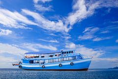 Passenger wooden boat floating on blue sea water with beautiful Royalty Free Stock Photo