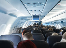 Passengers in airplane cabin interior. Overhead view of passengers travelling in airplane cabin interior economy class Stock Photos