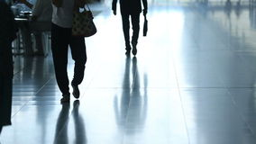 Passengers in airport transit terminal. Silhouette of young business man walking away with suitcase going traveling stock video