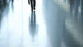 Passengers in airport transit terminal. Silhouette of young business man walking to camera with suitcase for travel.  stock footage