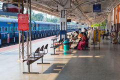 Passengers on Alleppey railway station. ALLEPPEY, INDIA - FEBRUARY 7: Platform under a shed with waiting passengers (unidentified) and a train at the Alleppey stock images