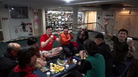 Passengers of an Asian-looking ferry have a picnic on the lower deck of the passenger liner.