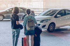 Passengers with big roller luggage stand to wait for the car to pick up stock photography