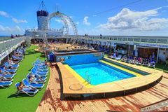 People relaxing on the spacious pool deck of a cruise ship stock photo