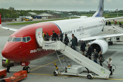 Passengers boarding airplane. Passengers getting aboard an airplane from Norwegian airlines Royalty Free Stock Photography