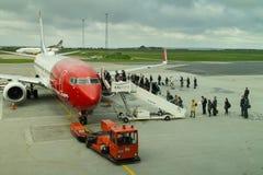 Passengers boarding airplane from Norwegian Airlines. Passengers getting aboard an airplane from Norwegian airlines Royalty Free Stock Photos