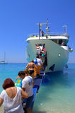 Passengers boarding a boat in azure nature Royalty Free Stock Photo