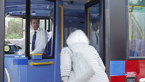 Passengers Boarding Bus Using Passes And Buying Ti stock footage