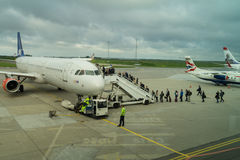Passengers boarding SAS airplane. Passengers getting aboard an airplane from scandinavian SAS airlinesnImage from Aalborg Airport AAL Stock Photo