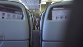 Passengers chairs inside cabin modern airplane while flying in sky. Passengers seats in economy class commercial plane. While flight. People traveling by stock footage