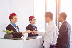 Passengers at check in counter. Airline passengers checking in at airline counter. Young women giving passport and ticket back to businessman at airport check in Stock Images