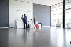 Passengers checkout at hotel reception. Passengers departing from business trip at hotel reception Royalty Free Stock Image