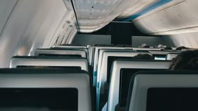 Passengers in comfortable seats of aircraft with maps on screens in chairs. Passengers in comfortable seats of aircraft with the screens in chairs stock footage