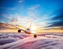 Passengers commercial airplane flying above clouds. Front view. Concept of fast modern travel royalty free stock images