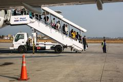 Passengers disembarking from a Qatar Airways flight at Tribhuvan International Airport. KATHMANDU, NEPAL - CIRCA JANUARY 2018: Passengers disembarking from a royalty free stock photo