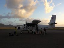 Passengers disembarking from a twin otter in the grenadines. Luggage and people arriving by 'plane at bequia in the windward islands stock footage