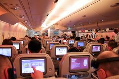 Passengers on an economy flight showing the seats and touch screens. Passengers flying economy on a commercial flight with built in tv screens Royalty Free Stock Photo