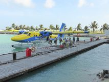 Passengers embarking floatplane. Passengers boarding a Trans Maldivian airways DHC Twin Otter seaplane at Male International Airport in the Maldives Royalty Free Stock Photos