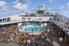 Passengers enjoy a day at sea on the top deck of cruise ship Stock Photos