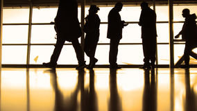 Passengers follow to boarding with baggage in front of window in airport, silhouette, warm Stock Photo