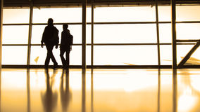 Passengers in front of window in airport, silhouette, warm Royalty Free Stock Image