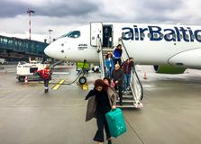 Passengers get off the Airbaltic plane arrived in Riga on a rainy day. Riga, Latvia - May 5, 2018: Passengers get off the Airbaltic plane arrived in Riga on a stock photo