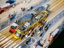 Passengers getting on light train in Warsaw. Modern tram collecting people on tram stop. View from above Royalty Free Stock Photography