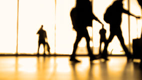Passengers going to boarding with baggage in front of window in airport, silhouette, warm Stock Photo