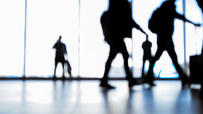 Passengers going to boarding with baggage in front of window in airport, silhouette Royalty Free Stock Photography