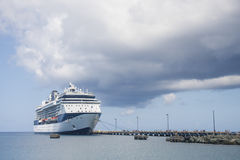 Passengers Leaving Cruise Ship Under Cloudy Skies Stock Image